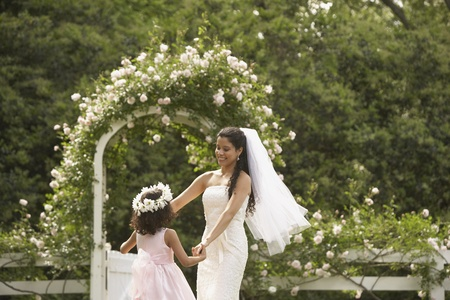 flowergirl: Hispanic bride and young girl dancing in circle LANG_EVOIMAGES
