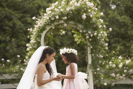 flowergirl: Hispanic bride and young girl smiling at each other