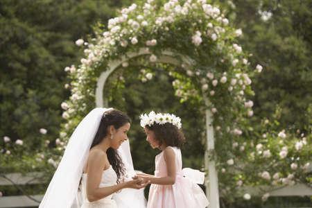 cérémonie mariage: Mariée et jeune fille hispanique souriant à l'autre