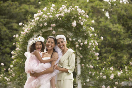 flowergirl: Hispanic bride with mother and young girl smiling