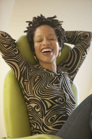 arms behind head: African woman laughing with arms behind head LANG_EVOIMAGES