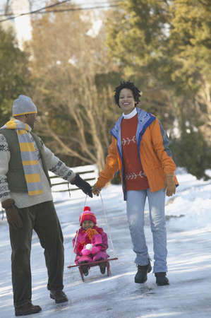 couple winter: African couple pulling child on sled