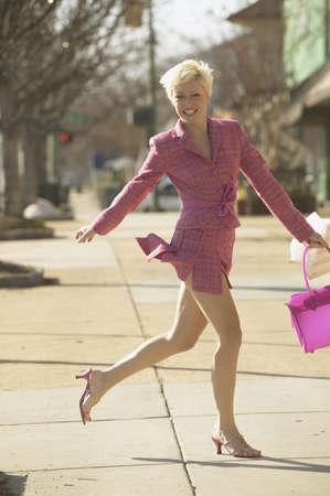 gentrification: Businesswoman running  on sidewalk
