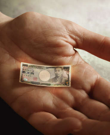Man's hand holding tiny Yen Stock Photo - 16092030
