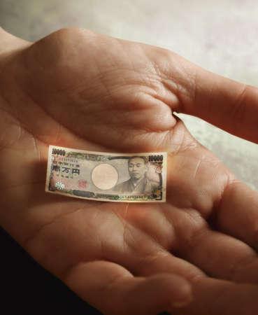 lower value: Mans hand holding tiny Yen LANG_EVOIMAGES