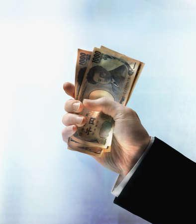 Businessman's hand holding Yen Stock Photo - 16092032
