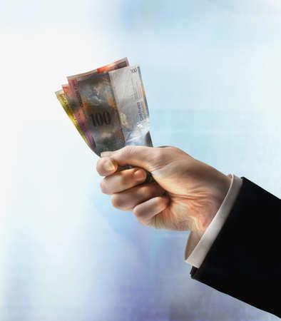 Businessman's hand holding Swiss Francs Stock Photo - 16092033