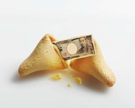 Broken fortune cookie with Yen inside Stock Photo - 16092036