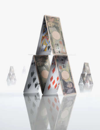 financial stability: Pyramid made of  Yen and playing cards LANG_EVOIMAGES