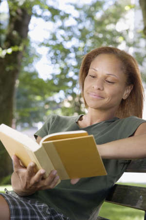 relishing: African woman reading on park bench