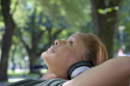 relishing: African woman wearing headphones in park LANG_EVOIMAGES