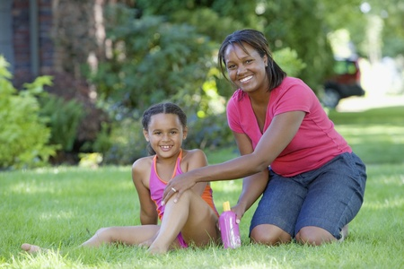 African mother putting sunscreen on daughter outdoors Stock Photo - 16092056
