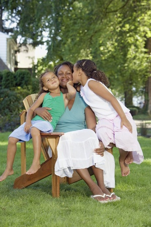 smooching: African mother and young daughters hugging outdoors