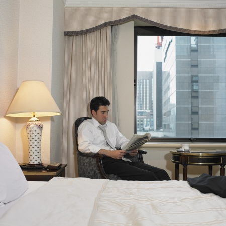 Asian businessman reading newspaper in hotel room Stock Photo