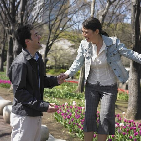 solicitous: Asian couple laughing and holding hands in urban park