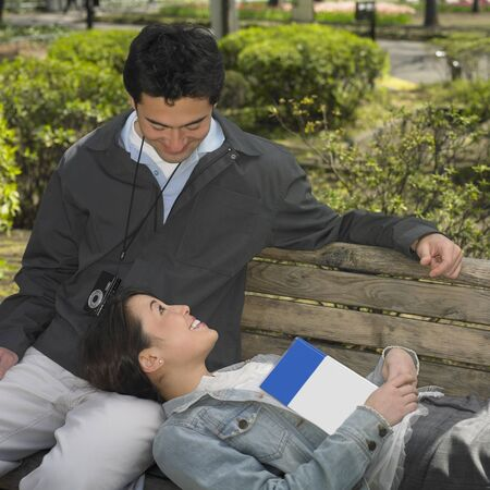 guidebook: Asian couple sitting on park bench with guide book LANG_EVOIMAGES