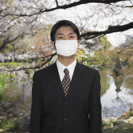 attired: Asian businessman wearing surgical mask in park LANG_EVOIMAGES
