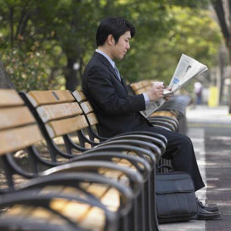 asian businessman: Asian businessman reading newspaper on park bench LANG_EVOIMAGES