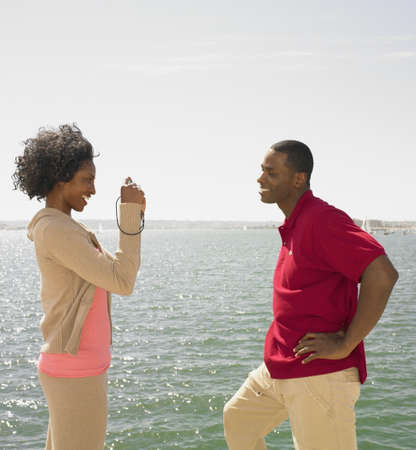 wooing: African woman taking photograph of African man next to water LANG_EVOIMAGES