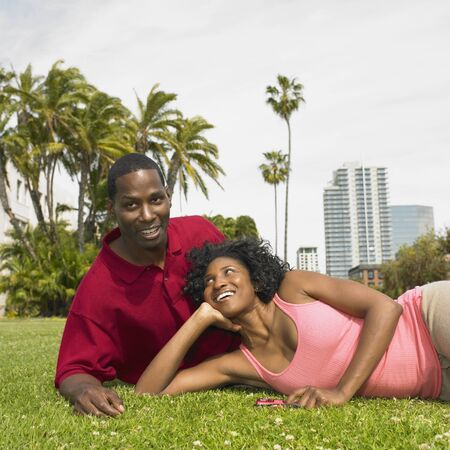 solicitous: African couple laying in grass smiling