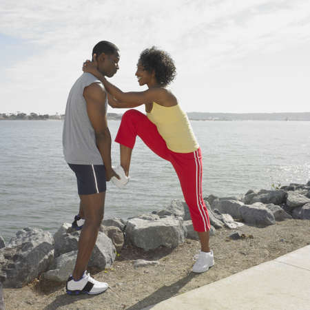 attentiveness: African couple in athletic gear stretching outdoors