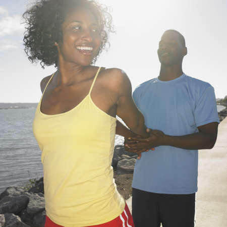 athletic gear: African couple in athletic gear stretching outdoors