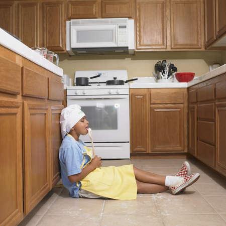 Hispanic boy licking wooden spoon in kitchen Stock Photo - 16092099