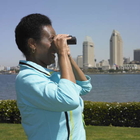 African woman using binoculars with cityscape in background
