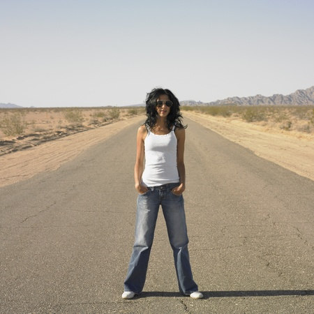 Woman standing in middle of deserted road Stock Photo