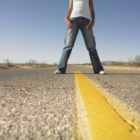 the road surface: Surface shot of woman standing in middle of deserted road