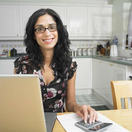 Hispanic woman at kitchen table paying bills Stock Photo - 16092114