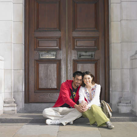 solicitous: Asian couple sitting in doorway in London LANG_EVOIMAGES