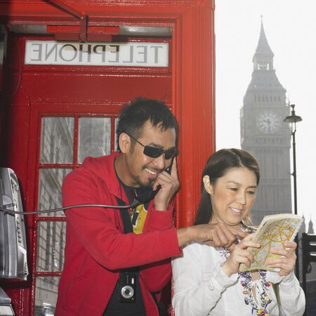 finding a mate: Asian couple using public telephone box and map in London