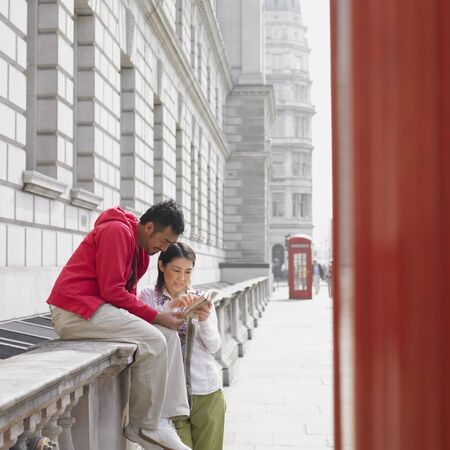 finding a mate: Asian couple looking at map in London