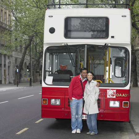 motorcoach: Asian couple hugging in front of tour bus in London