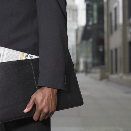 Close up of African businessman holding briefcase
