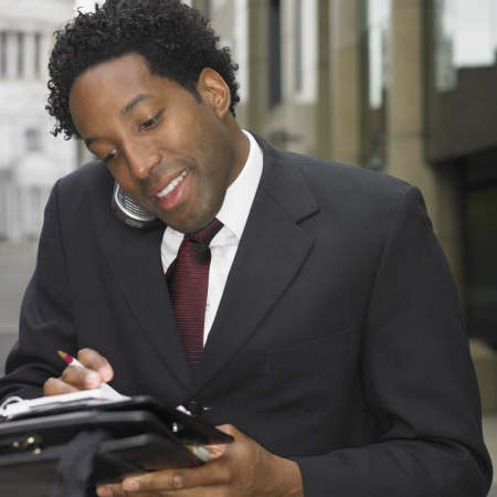 African businessman using cell phone outdoors Stock Photo