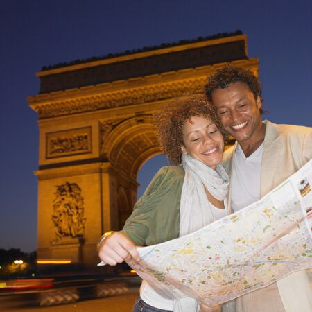 finding a mate: Couple looking at map in Paris at night LANG_EVOIMAGES