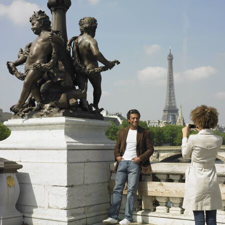 Woman taking photograph of man next to statue in Paris Banque d'images