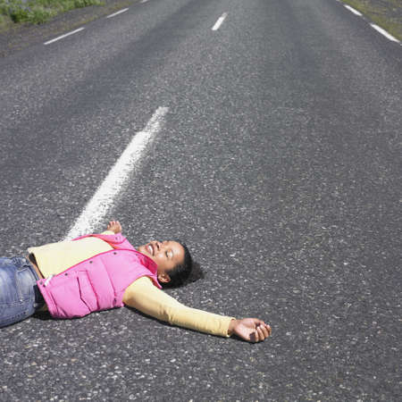 jeopardizing: Young woman laying in middle of road smiling