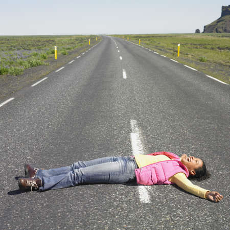 jeopardizing: Young woman laying in middle of road laughing  LANG_EVOIMAGES