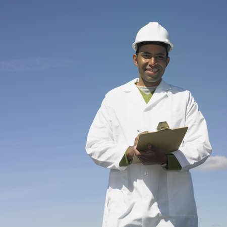 Man with hard hat and clipboard smiling outdoors Stock Photo - 16092168
