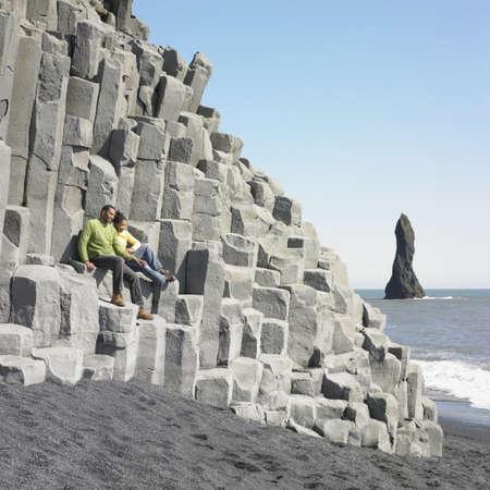 longshot: Couple sitting on rock ledge at beach