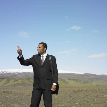 Businessman pointing in deserted rural area Stock Photo - 16092170
