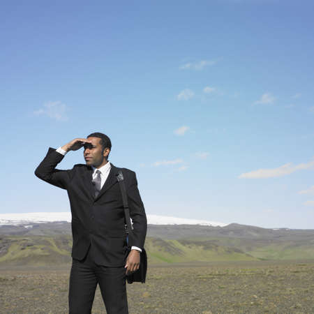 Businessman shading eyes in deserted rural area Stock Photo - 16092171
