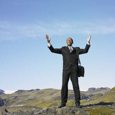 Businessman smiling with hand raised in deserted rural area Stock Photo - 16092172