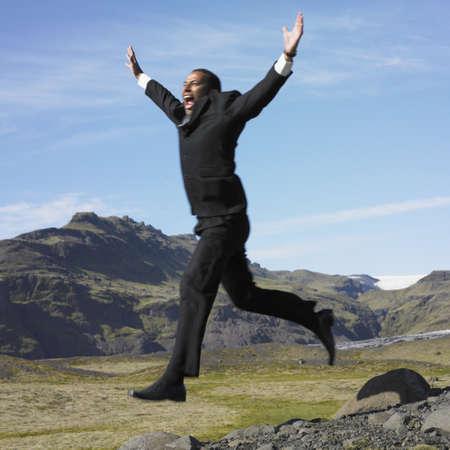 unconcerned: Empresario saltando desde las rocas en el �rea rural desierta