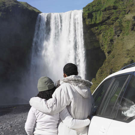 man waterfalls: Couple in winter clothes looking at waterfall