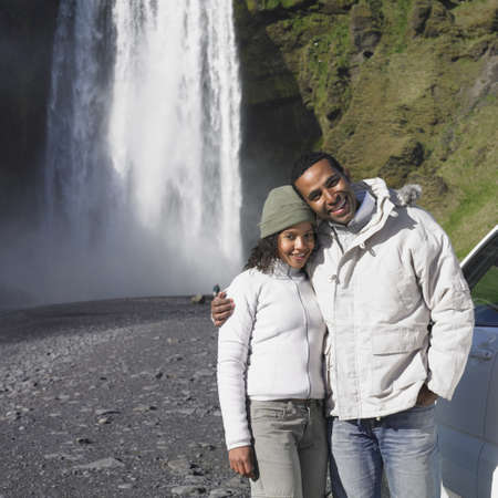 Couple in winter clothes hugging in front of waterfall Stock Photo - 16092176