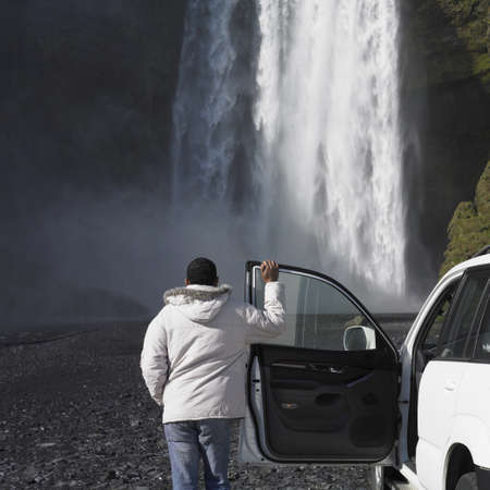 Man in winter jacket leaning on truck and looking at waterfall Stock Photo - 16092177